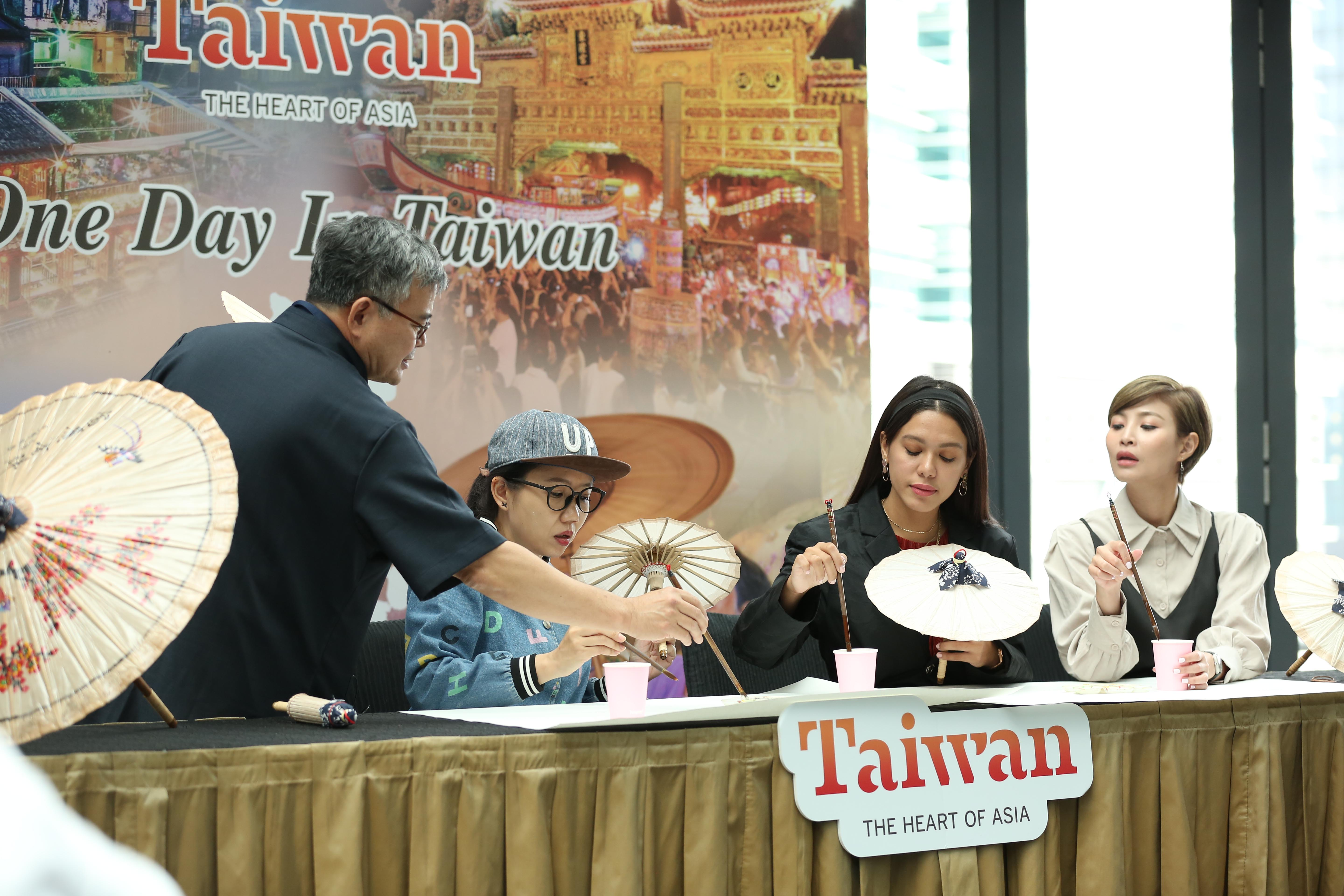 Oil-paper umbrella master from Taiwan  teaches YouTuber Cjlee (left 2), influencer Julia Farhana Marin and artist Janelle Chin(right) how to pain on this traditional umbrella.